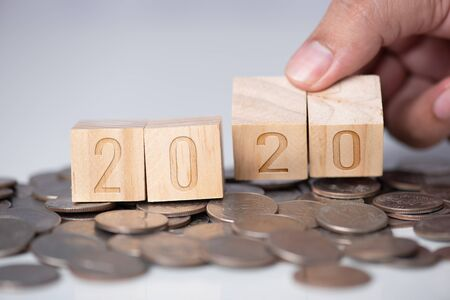 hand open wood cube with text year 2020 on the coins