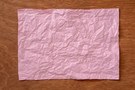 crumpled paper sheet on wood background Banco de Imagens