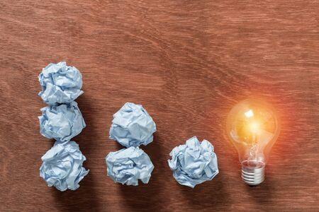 decrease crumpled paper to light bulb on wood background Banco de Imagens
