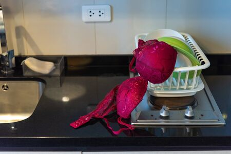 red woman bra on stove in the kitchen Banco de Imagens