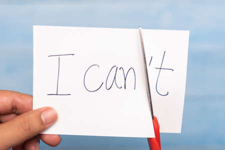 hand cutting the letter t of the written word I can't , motivation concept Archivio Fotografico