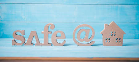 wood text safe at home on light blue wood background Archivio Fotografico