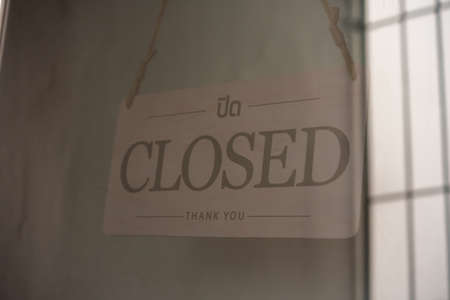 closed sign board hanging at the door