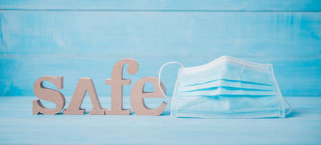 wood text safe and face mask on light blue wood background Archivio Fotografico