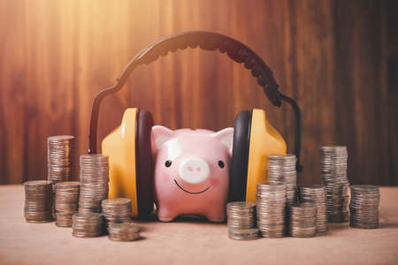 piggy bank is covered with headphones to reduce noise complain from all around and coins stack, saving plan