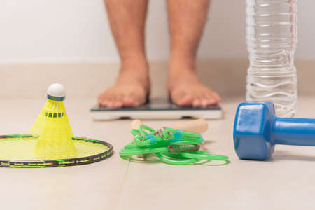 Simple exercise equipment with man on weighing machine , weight loss concept
