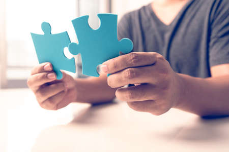 man hand connecting jigsaw puzzle pieces