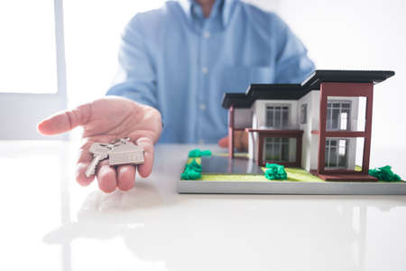 man hand offering house key with house model background