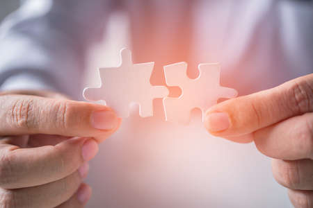 business man hand connecting jigsaw puzzle pieces