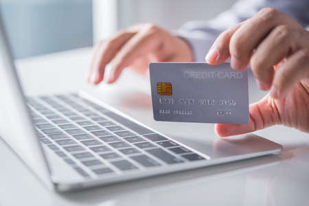 man hand holding credit card and using laptop