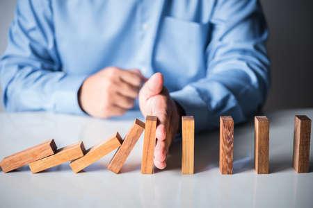 man hand stop domino falling effect Archivio Fotografico
