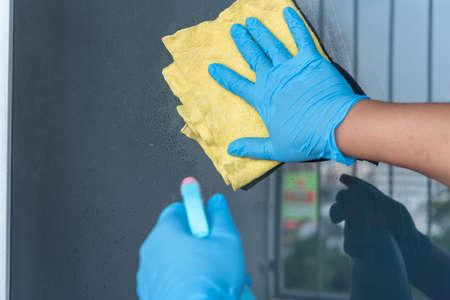 man hand ware rubber glove cleaning door glass window