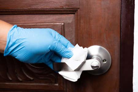 man hand wear rubber glove cleaning door knob