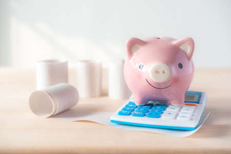 piggy bank on calculator with many bills that must be paid Archivio Fotografico