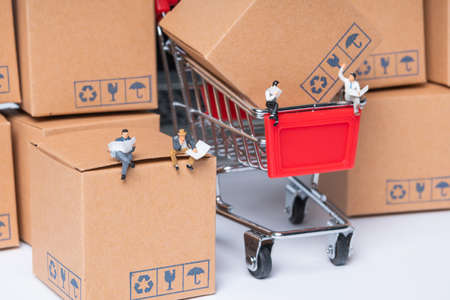 miniature people sitting on parcel box, online shopping concept