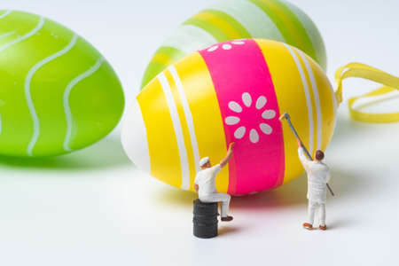 miniature people painting colorful patterns on  easter eggs