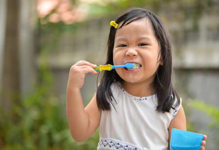 Cute Asian kid brushing teeth photo