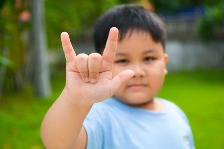 asl sign: Cute boy show love hand symbol