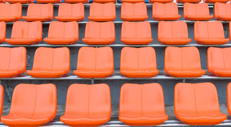 orange color: orange grandstand chairs Stock Photo