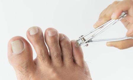 clipper: nail clipper cutting man toenails by little hand
