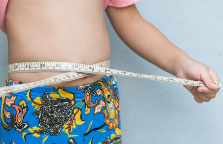 fatness: Little girl measuring her stomach