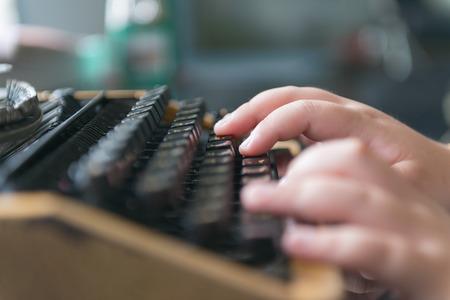 Boy hands writing on old typewriter