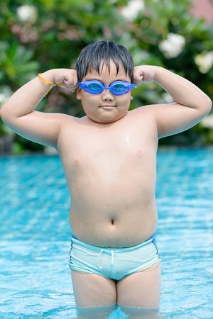 obesidad infantil: chico gordo asiático mostrándole muscular en la piscina.