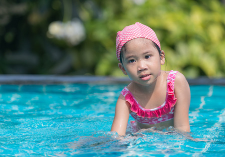 pink bikini: Little cute Asian girl on bikini suit in pool