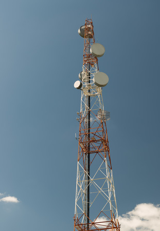 communication tower: Telecommunications antenna for radio television and telephone white cloud and Blue sky