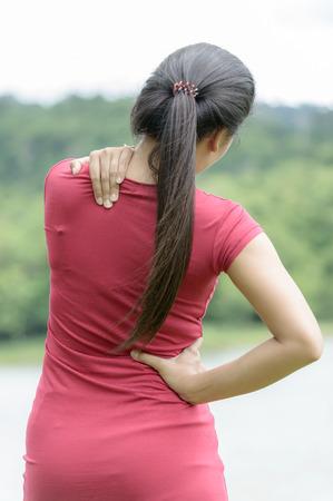 neck girl: Woman massaging pain back on nature background