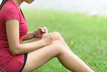 Leg Pain In A Woman on green background Stock Photo