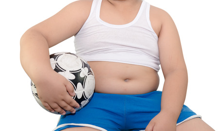 overweight kid: fat boy and football isolated on white background