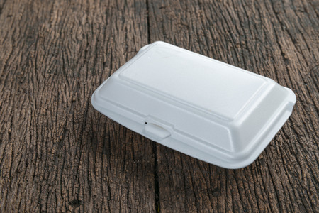 plastic waste: White foam box on old wood background