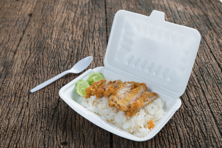 fried chicken with rice in foam box on wood background