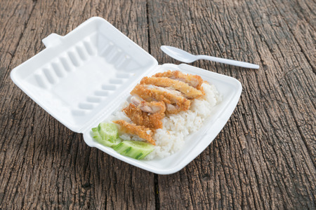 plastic waste: fried chicken with rice in foam box on wood background