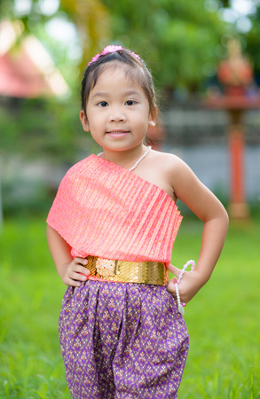 thai style: Cute asian girl wearing typical thai dress on nature background