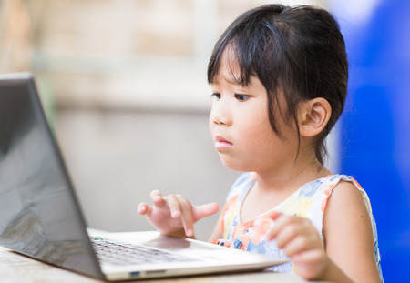 playing video games: education, school, technology and internet concept - Cute girl with laptop pc at home