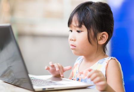 niñas jugando: la educación, la escuela, la tecnología y el concepto de Internet - Linda chica con PC portátil en casa Foto de archivo