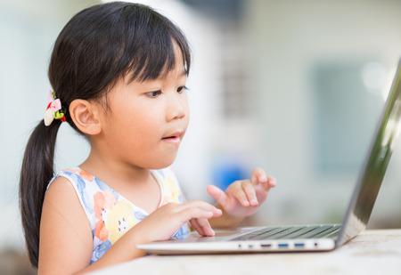 ni�os jugando videojuegos: la educaci�n, la escuela, la tecnolog�a y el concepto de Internet - Linda chica con PC port�til en casa Foto de archivo