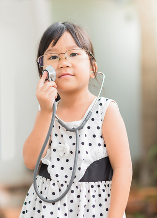 cute little girl smiling: Cute asian girl play in doctor costume.
