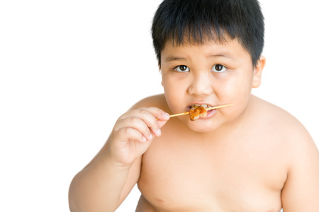 overweight kid: asian fat boy eat grilled pork isolated Stock Photo
