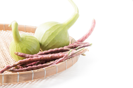 cocina saludable: bottle gourd fruit and purple cowpea in basket isolated on white
