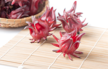 bamboo mat: roselle fruit on bamboo mat isolated on white Stock Photo
