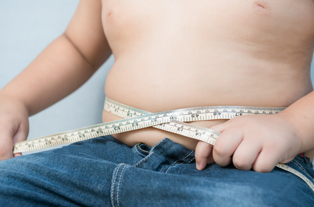 fatness: Fat boy measuring his belly with measurement tape on gray background