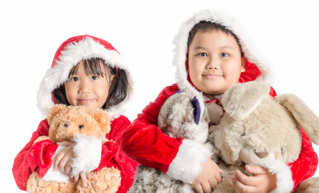 boy lady: Asian girl and boy in santa costume hugging bear doll on christmas isolated Stock Photo