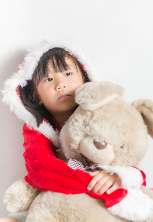 petite fille triste: Peu de graisse asiatique gar�on � santa costume d'attente pour des cadeaux de No�l sur fond blanc