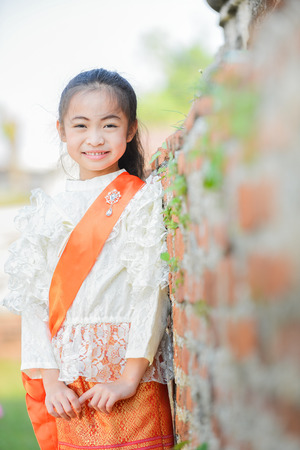 mignonne petite fille: Cute little girl wearing typical thai dress on temple background