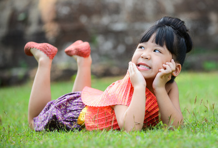 mignonne petite fille: Cute little girl wearing typical thai dress play on field