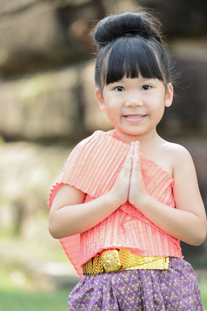 cute little girl: Cute little girl wearing typical thai dress pay respect on temple background
