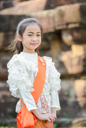 young style: Cute little girl wearing typical thai dress on temple background